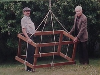 A picture of two men, with an odd-looking wooden frame