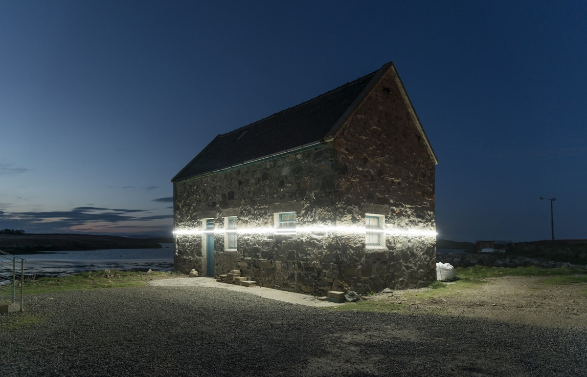art installation shows future sea level on side of building in Scotland with line of light
