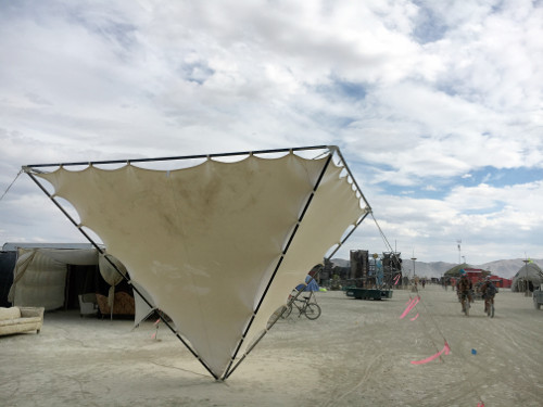 Photo of an inverted pyramid made out of metal and fabric, installed in the desert